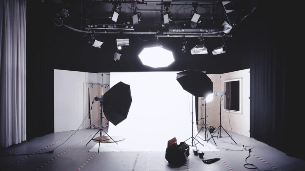 Estudio de fotografía con focos y fondo blanco.